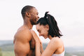 Close-up of sexy fit mixed race couple with perfect bodies in sportswear softly embracing on mountains landscape Royalty Free Stock Photo