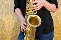 Close up on a shiny brass tenor saxophone being played by young female musician standing in front of hay bale outdoors Royalty Free Stock Image