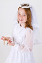 Close up shot above young girl smiling her first communion dress veil holding her rosary beads cross Stock Photo