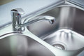 Close up shot for the clean chrome tap and washbasin in a kitchen Royalty Free Stock Photography