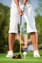 Close up shot of golfer ready to tee off golf ball on green grass with the driver positioned hit the ball Stock Photo