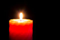 Close up shot of red burning candle on dark background Stock Image