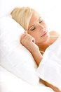 Close up shot of sleepy woman in bed lying on the white cushion Royalty Free Stock Photography