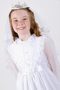 Close up shot slightly below young girl smiling her first communion dress veil Royalty Free Stock Image
