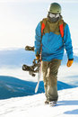 Close up shot of a snowboarder walking at the top of a mountain at golden hour Royalty Free Stock Photo