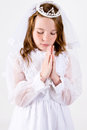 Close up shot straight young girl praying her first communion dress veil Stock Images