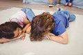 Close-up of siblings relaxing on carpet Royalty Free Stock Photo