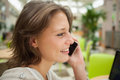 Close up side view of a woman using mobile phone young in the cafeteria Royalty Free Stock Photography