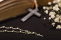 Close up of a silver rosary beads and a blurred white small flowers with rosary beads over a holy bible, black Royalty Free Stock Photo