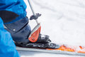 Close up of ski pole unfasten boot from ski skier getting his untight unrecognizable Royalty Free Stock Photo