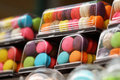 Close-up small French colorful macarons in glossy plastic container in franch restaurant Royalty Free Stock Photo