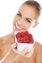 Close up of smiling blonde holding raspberries Royalty Free Stock Photo