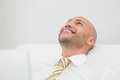 Close up of smiling elegant young businessman looking up a on sofa at home Royalty Free Stock Photography
