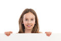 Close up of smiling girl behind placard portrait young holding blank sheet head and shoulders studio shot isolated on white Royalty Free Stock Image