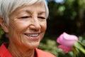 Close-up of smiling senior woman looking at fresh pink rose Royalty Free Stock Photo