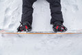 Close up of a snowboard with bindings and the boots hooked in the is on the snowy ground with perfect Stock Images