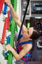 Close up of sportswoman climbing in indoor rock climbing center a who is on the wall Stock Image