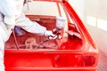 Close-up of spray paint gun with worker working on a red car Royalty Free Stock Photos