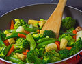 Close up of stir fry vegetables frying pan with and wooden spoon Stock Photo
