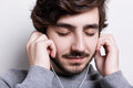 A close-up of a stylish guy with dark hair and beard enjoing listening to the music with his earphones having closed eyes holding