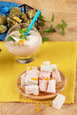Close-up of sweet snacks. Turkish delight with a glass of banana milkshake on a wooden background. Refreshment concept. Royalty Free Stock Photo