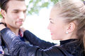 Close up sweet young lovers smiling to each other and admiring while holding at the park on daytime Royalty Free Stock Photo