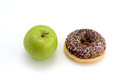 Close-up of tasty chocolate donut and fresh green apple on white background suggesting healthy eating concept Royalty Free Stock Photo