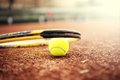 Close up of tennis ball and racket on clay court summer day at Stock Photo