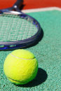 Close up of tennis racquet and ball on the clay court Royalty Free Stock Photography
