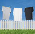 Close up of three t shirts on the rope grey white and dark grey outside background with sky green grass Stock Photo