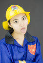 Close up of a tired lady firefighter poking out tongue young attractive asian woman in her s shot in studio on white background Stock Photography