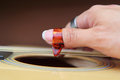Close up to pick acoustic guitar in the hand Royalty Free Stock Image