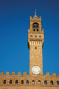 Close-up of the tower with clock from the Palazzo Vecchio to the sunset in Florence. Royalty Free Stock Photo
