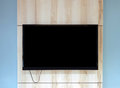 stock image of  Close up of TV set on wooden wall hanging above bench in office