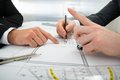 Close-up of two architects working on blueprint