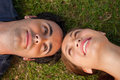 Close-up of two friends looking at each other while lying head t Royalty Free Stock Images