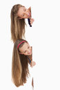 Close-up of two smiling long hair students behind a blank sign Royalty Free Stock Photos