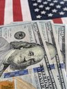 close-up of United States $100 bills against United States flag. Royalty Free Stock Photo