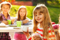 Close up view of blond girl holding cupcake with her friends sitting at table with teacups on background at sunny autumn day Stock Photo