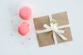 Close-up view of decorative kraft envelope with bow and pink macarons isolated on white