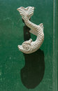 Close-up view of the fish shaped knocker on a green wooden door Royalty Free Stock Photo