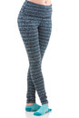Close up view of fit woman legs in colourful striped sports trousers and blue socks standing in fifth ballet position Royalty Free Stock Photo