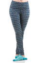Close up view of fit woman legs wearing colourful striped sports trousers and blue socks from front view in crossing position Royalty Free Stock Photo