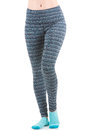 Close up view of fit woman legs wearing colourful striped sports trousers and blue socks from front view with one leg raised at th Royalty Free Stock Photo