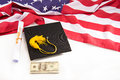 Close-up view of graduation mortarboard, diploma, dollar banknotes and us flag on white Royalty Free Stock Photo