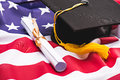 Close-up view of graduation mortarboard and diploma on US flag Royalty Free Stock Photo