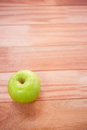 Close up view of an green apple on wooden desk Stock Photography