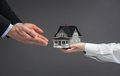 Close up view of hands giving house model to other hands home concept realty and deal Stock Images