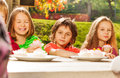 Close up view of happy children sitting together at table drinking tea with cupcakes during sunny autumn day Royalty Free Stock Images