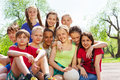 Close up view of happy teenagers sitting close to each other in a hug outside during summer sunny day Royalty Free Stock Photos